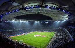 A large sports stadium lit up during the night game from the view of the upper stadium stands