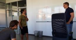 Three guys discussing the inputs from the whiteboard behind them in the office space