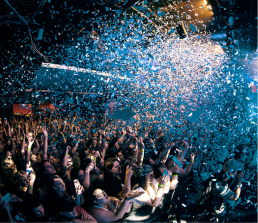 A large group of people enjoying a music event under the confetti rain