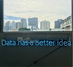 A window overlooking skyscrapers and 'Data has a better idea' written with neon lights under the window sill